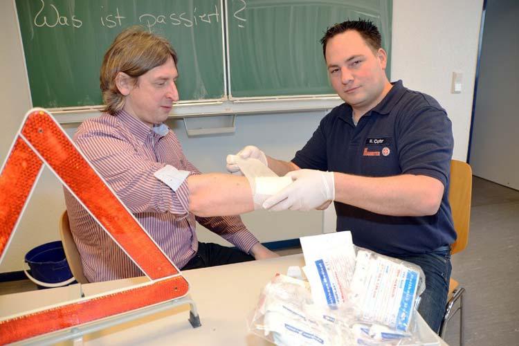 Marcel Colter demonstriert an Stefan Greiber, wie man einen Verband anlegen sollte.