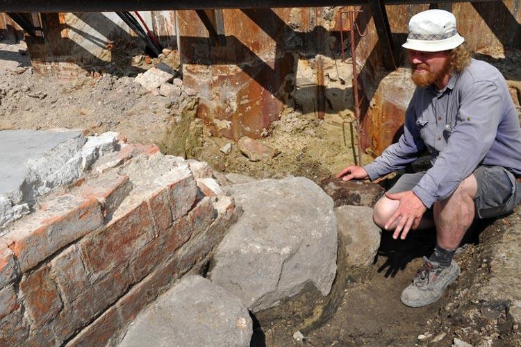 Archäologe Thies Evers zeigt das Fundament eines Turmes, das aus Eichenhölzern, Findlingen und Ziegeln besteht.