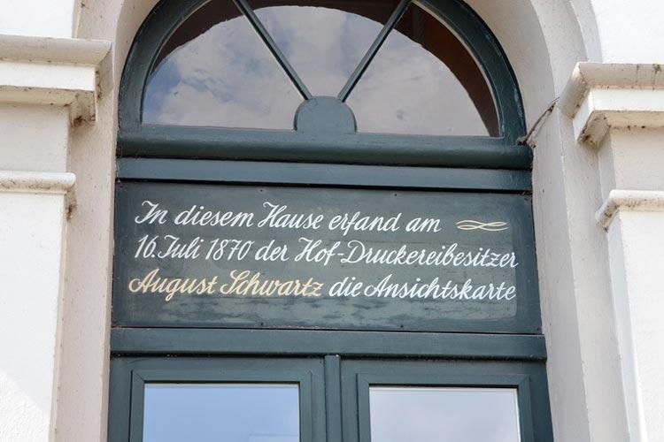 Der Hinweis über der Haustür weist auf die Erfindung der Postkarte hin.