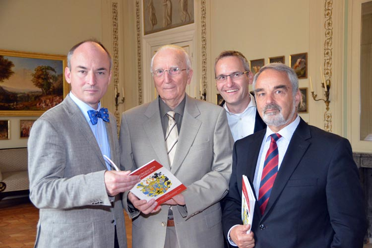 Die Autoren Dr. Jörgen Welp, Manfred Furchert, Verleger Florian Isensee und Landschaftspräsident Thomas Kossendey (von links) stellten das Wappenbuch vor.