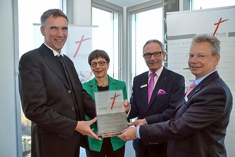 Bischof Jan Janssen und Renate Giesler von der EKD überreichten Martin Grapentin und seinem Vorstandskollegen Gerhard Fiand (von links) das Arbeitsplatzsiegel Arbeit plus.
