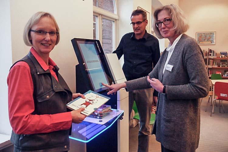ibliotheksleiterin Heike Janssen, Bernd von Seggern, EDV-Koordinator des Fachdienstes Bibliotheken, und Marianne Reudnik, Leiterin Kinderbibliothek, (von links) beim einem der drei Selbstbedienungsgeräte in der Kinderbibliothek.