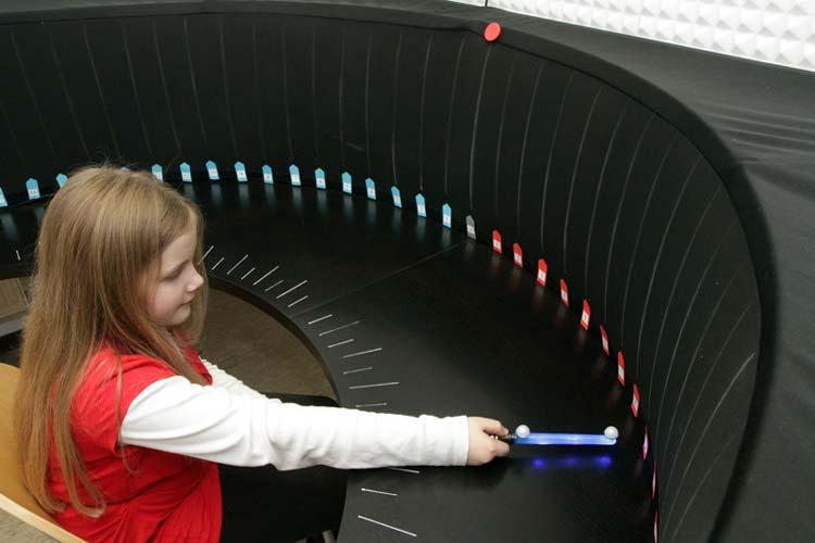 Grundschüler sitzen am Audiometrietisch und bestimmt die Richtung, aus denen die Geräusche kommen.