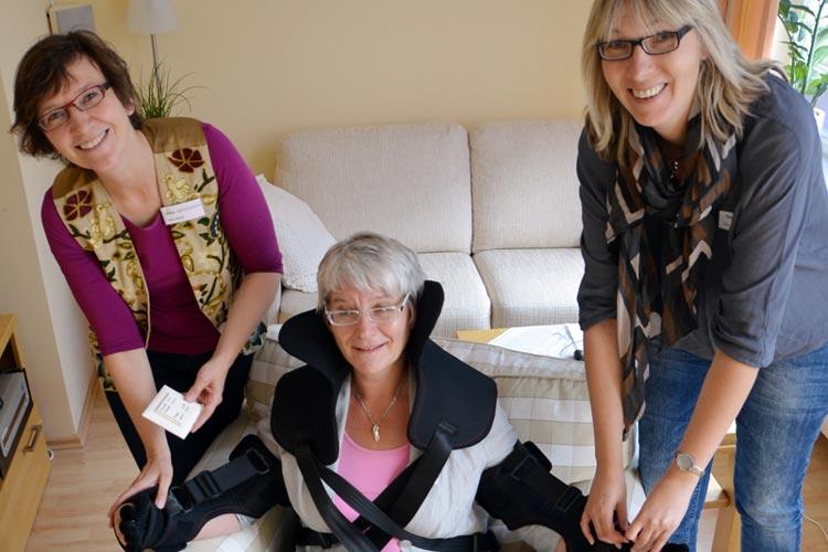 Heimke Möhlenhof hat sich den Alterssimulationsanzug übergezogen und versucht mit Hilfe von Delia Balzer und Regina Neuke aus dem Sessel zu kommen.