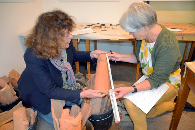 Margarete Rosenbohm-Plate und Claudia Kossendey vermessen alte Dachpfannen.