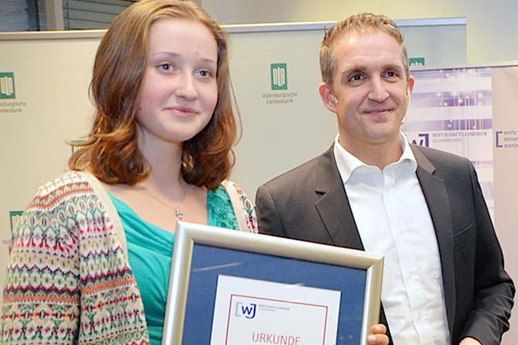 Paula Stöhr vom Neuen Gymnasium Oldenburg nahm stellvertretend für ihre Klasse 9d den Hauptpreis der Wirtschaftsjunioren, ein Besuch eines Heimspiels der EWE-Baskets, aus den Händen von Frank Glaubitz entgegen.