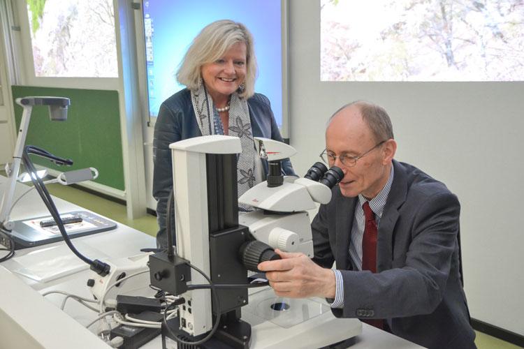 Vizepräsidentin Gunilla Budde und Präsident Hans Michael Piper testen die neuen Mikroskope im Hörsaal der Uni Oldenburg.