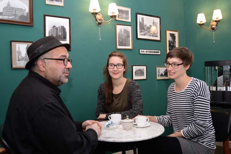 Werkstattfilm-Leiter Farschid Ali Zahedi, Stella Rüger und Yvonne Resch im Café des KinOLadens vor Fotografien aus den 20er Jahren.