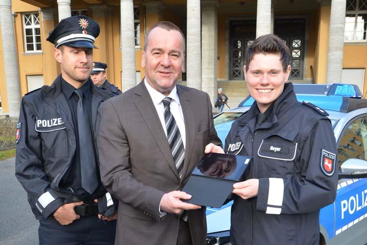 Innenminister Boris Pistorius überreicht den Polizisten Anja-Marina Meyer und Jens Rodiek das neue Tablet.