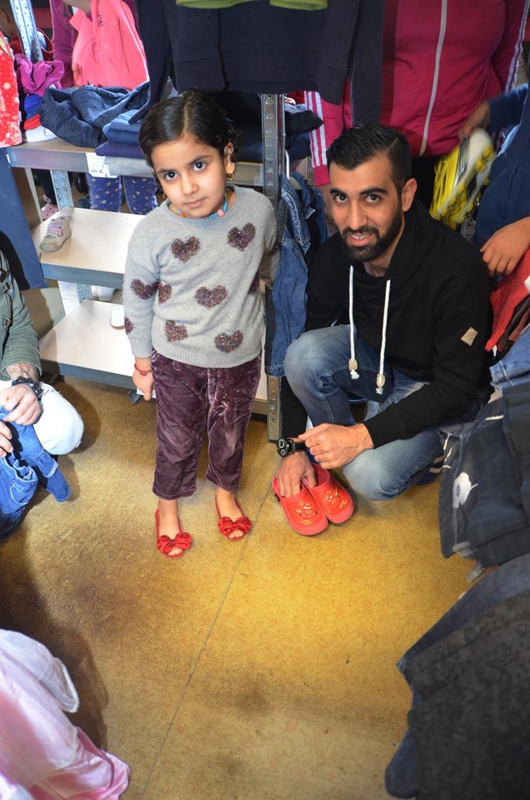 Zusammen mit ihrem Vater hat dieses kleine Flüchtlingsmädchen ein paar rote Schuhe entdeckt und ist glücklich.