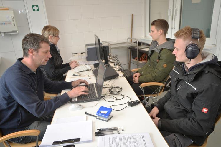 Die Auszubildenden Kevin Lemping und Maximillian Hantel nehmen am Hörtest teil, den Matthias Selchow und Margrit Lehnen, beide Arbeitsmedizinische Assistenten der BG Bau, durchführen.