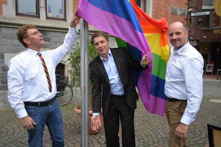 LuST-Vorsitzender Klemens Sieverding, Oberbürgermeister Jürgen Krogmann und LuST-Pressesprecher Kai Bölle hissen die Regenbogenfahne am Oldenburger Rathaus.