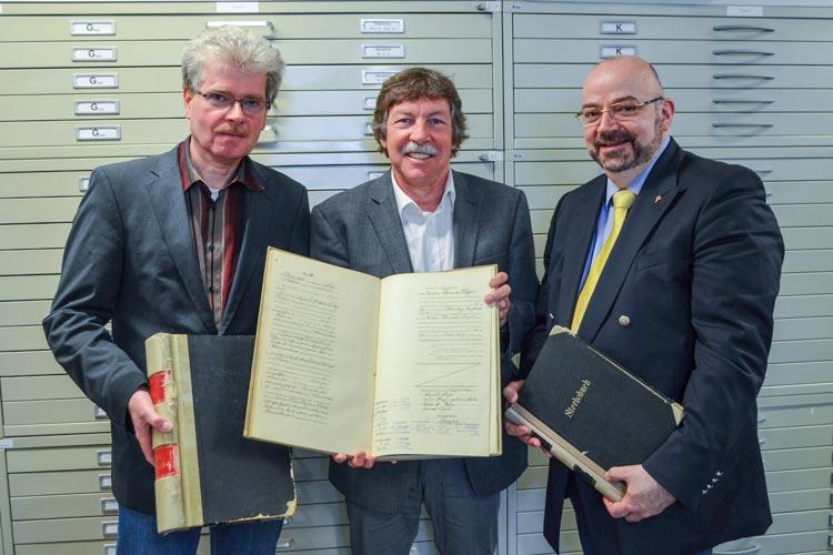 Oldenburgs Stadtarchivar Claus Ahrens mit Wolfgang Grams und Nikolai Donitzky von Ancestry zeigen einen von über 500 Bänden, die digitalisiert worden sind.