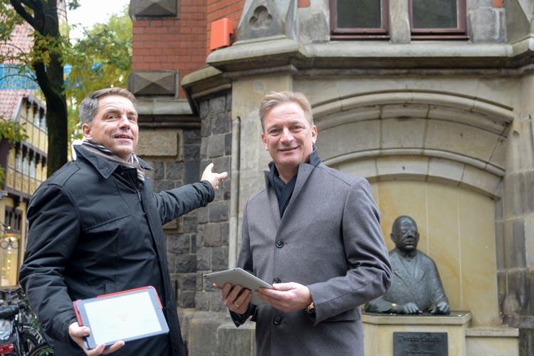 Jürgen Krogmann und Matthias Brückmann gehen vor dem Alten Oldenburger Rathaus mit den neuen WLAN-Hotspot online.