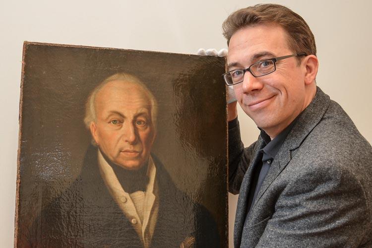 Marcus Kenzler zeigt das Gemälde von Herzog Peter Friedrich Ludwig, das eines Tages sorgsam verpackt im Innenhof des Oldenburger Schlosses lag.