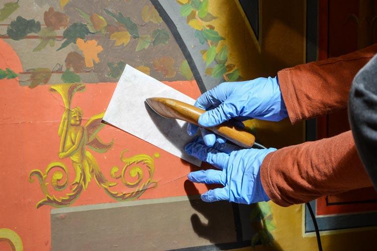 Christiane Maier fügt die gerissene Tapete wieder zusammen und bügelt sie.