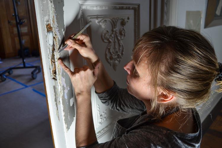 Britta Dierig löst mit einem Skalpell die einzelnen Farbschichten von der Holztür.