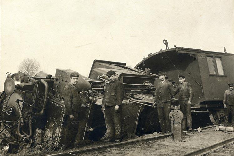 Eisenbahner vor einem entgleisten Zug, um 1900.