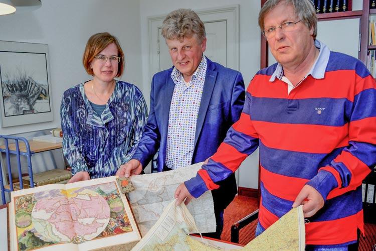 Corinna Roeder, Michael Remmers und Michael Recke zeigen einige besondere Kartenexemplare die in der Ausstellung Fakten oder Fantasie – Karten erzählen Geschichten in der Landesbibliothek Oldenburg zu sehen sind.
