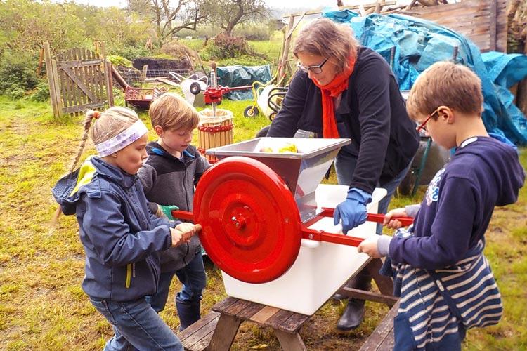 Antje Bruns-Osolin mit Schülern an der Hand-Obst-Mühle.