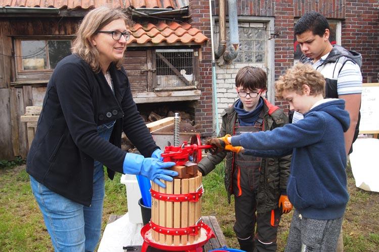 Antje Bruns-Osolin mit Schülern an der kleinen Saftpresse.