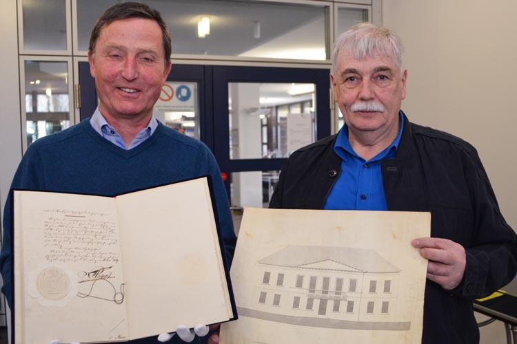 Dr. Wolfgang Henninger und Dr. Matthias Nistal (von links) zeigen das Original der ersten Verfassung  des Staatsgrundgesetzes von 1849 sowie eine Originalzeichnung des einstigen Landtages und heutigen Standesamtes in Oldenburg am Pferdemarkt.