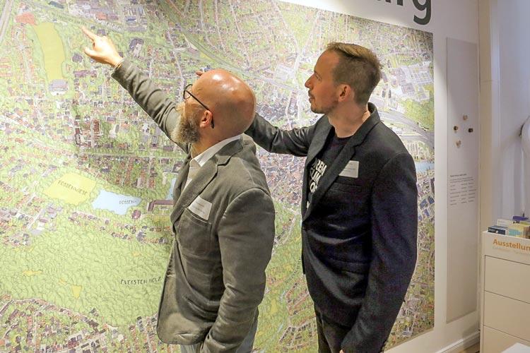 Illustrator Detlef Krause (links) und Computergrafiker Thiemo Eddiks vor ihrem überdimensionalen, detailgetreuen Oldenburg-Stadtplan in 3D-Optik.