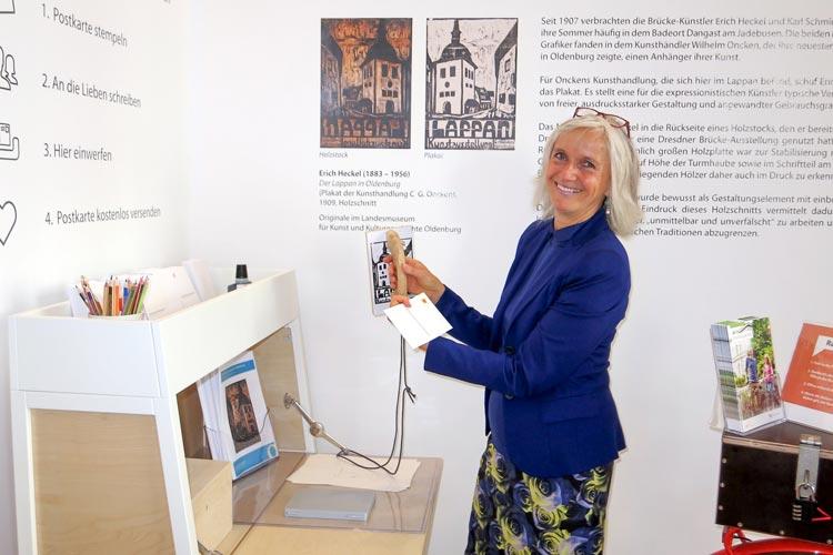 Silke Fennemann präsentiert die Postkarten-Station bei der die Gäste eine Postkarte mit dem Lappan-Motiv stempeln und mit einem Gruß kostenlos versenden können.