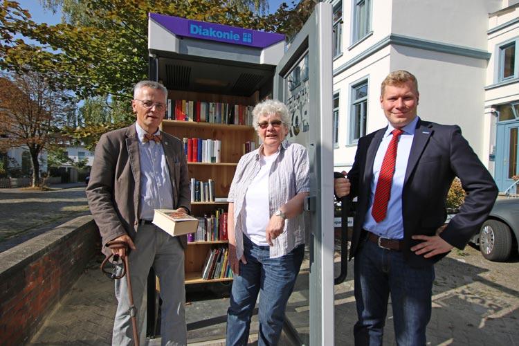 Diakonie-Vorstand Uwe K. Kollmann, Anwohnerin Ulla Meyer und Vorstandsassistent Benjamin Wehage übergeben die Bücherbox ihrer Bestimmung.