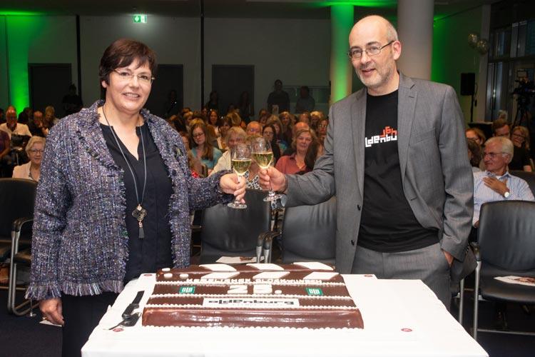 Karin Katerbau und Torsten Neumann vor der Jubiläumstorte im OLB-Saal.