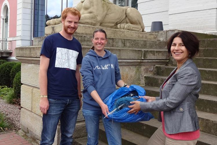Jonathan Tosberg und Melanie Klock überreichen den gesammelten Meeresmüll an Museumsdirektorin Dr. Ursula Warnke.