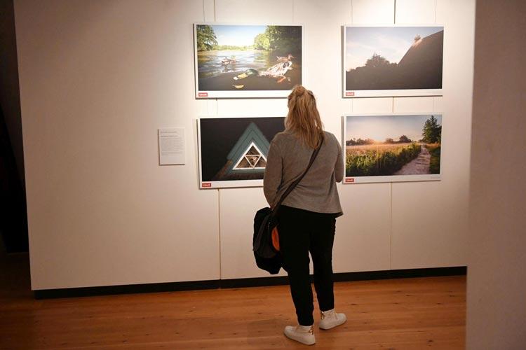 """Eine Besucherin vor den Bildern des Fotografen Dominik Janoschka in der Fotoausstellung """"Drei Tage in Oldenburg"""" im Schloss."""