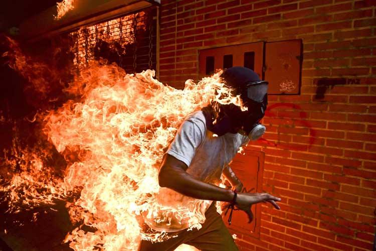 Am 3. Mai 2017 kam es in Venezuelas Hauptstadt Caracas zu Zusammenstößen zwischen Demonstranten und der Nationalgarde, bei denen Demonstranten Feuer auslösten und Steine schleuderten. Der 28-jährige José Víctor Salazar Balza fing Feuer, als der Benzintank eines Motorrads explodierte. Er überlebte mit Verbrennungen ersten und zweiten Grades. Das Foto wurde zum Pressebild des Jahres gewählt.