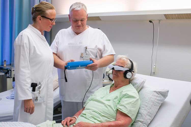 Dr. Ulrike Raap und Matthias Wilke legen die Einstellungen am sogenannten Media-Center der Videobrille fest – die Patientin kann über eine Fernbedienung die Inhalte der ablenkenden Filme steuern.
