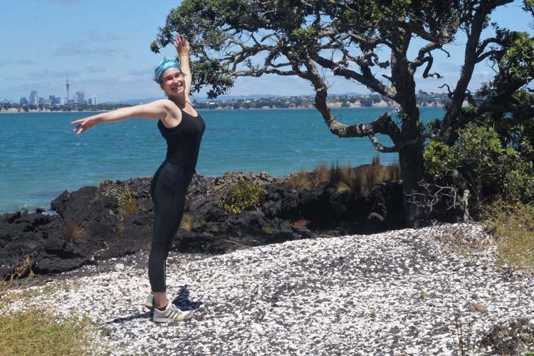 Danielle Zollickhofer auf Rangitoto Island, einer Vulkaninsel vor der Küste von Auckland. Links im Hintergrund ist die Skyline Aucklands zu sehen. Danielle Zollickhofer on Rangitoto Island, an ancient volcano in front of Auckland's shore. The skyline of Auckland can be seen on the left side of the picture.