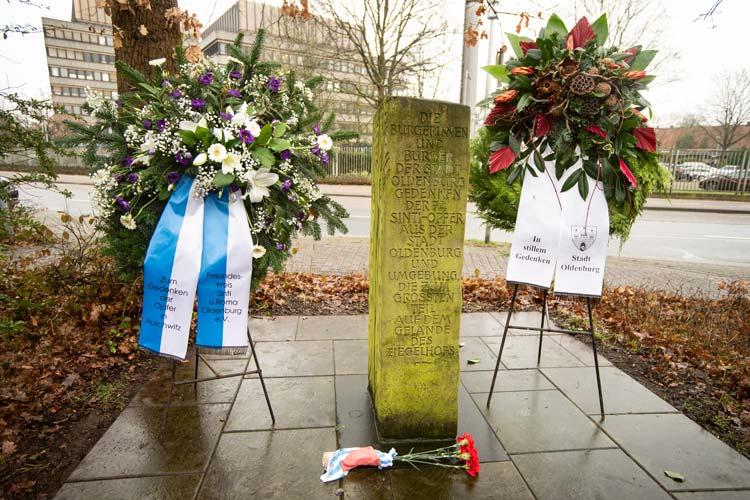 Kränze an dem Gedenkstein zur Erinnerung an die 74 Deportierten und Ermordeten Sinti und Roma aus Oldenburg.