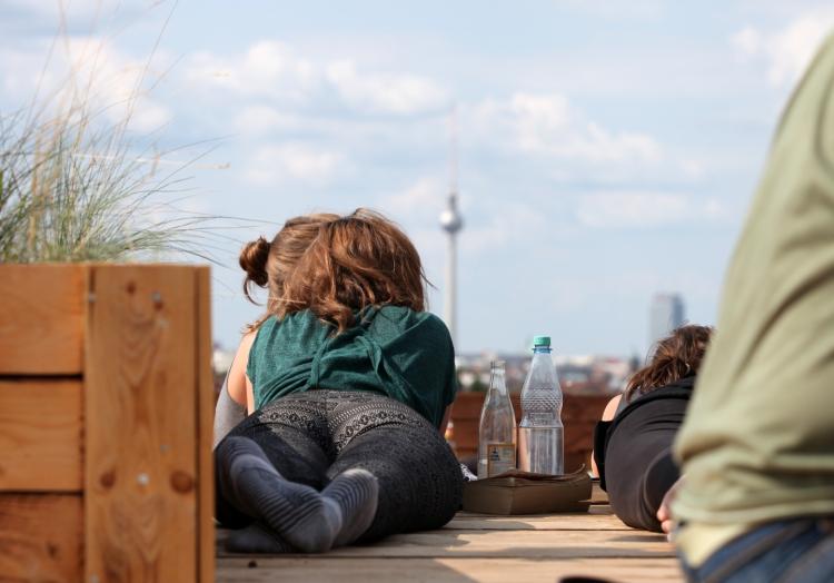 Junge Frau mit Getränken auf einer Dachterrasse mit Blick auf Berliner Fernsehturm, über dts Nachrichtenagentur