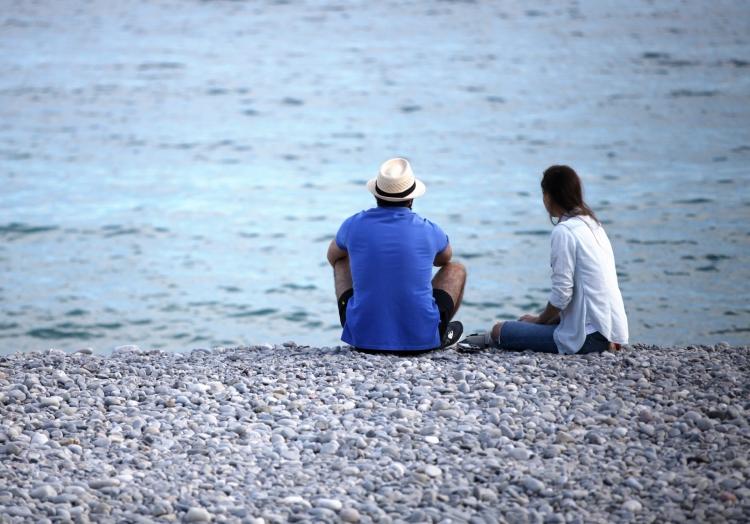 Mann und Frau sitzen am Strand, über dts Nachrichtenagentur