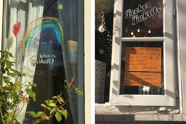 """Beispiele der Corona-Krise aus Oldenburg: Fensterbild """"Wir bleiben zu Hause"""" und ein Hinweis auf Lakritzversand zu Ostern."""