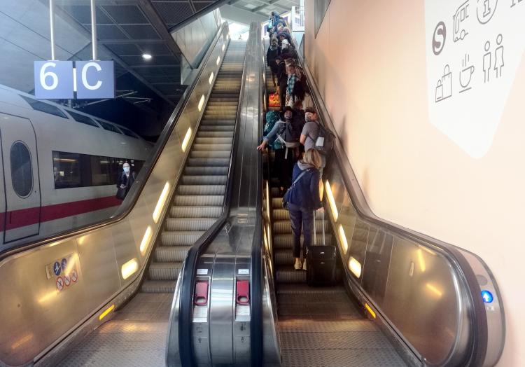 Menschen mit Schutzmasken auf einer Rolltreppe, über dts Nachrichtenagentur