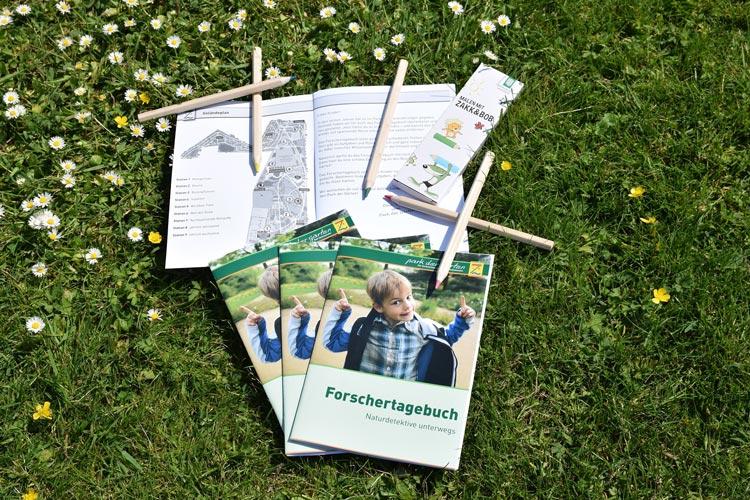 Ein Forschertagebuch liegt samt Stiften kostenlos für Naturdetektive aus.