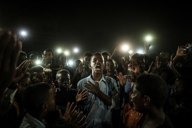 Yasuyoshi Chiba aus Japan wurde für sein Bild vom Aufstand im Sudan mit dem Hauptpreis ausgezeichnet. Ein junger Mann, der von Mobiltelefonen beleuchtet wird, rezitiert Gedichte, während Demonstrant*innen gegen den sudanesischen Diktator protestieren.