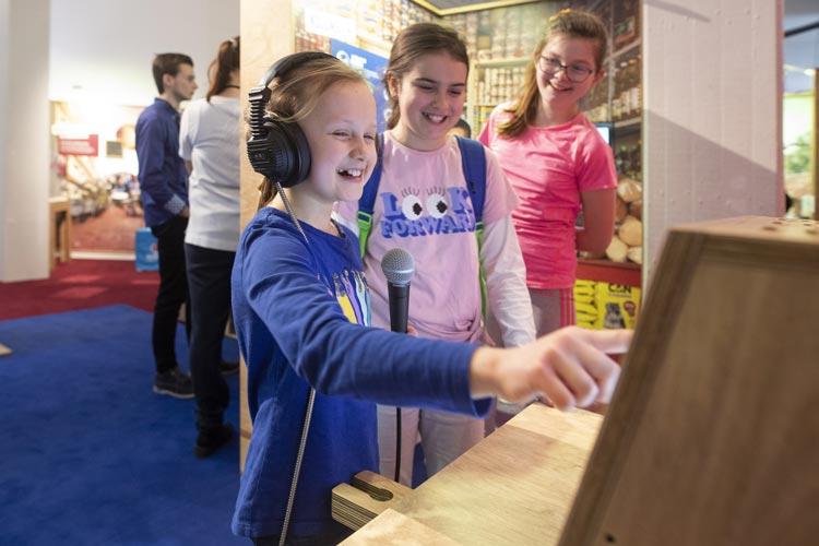 Kinder stehen an einer Mitmach-Station in der Ausstellung Mission 2030.